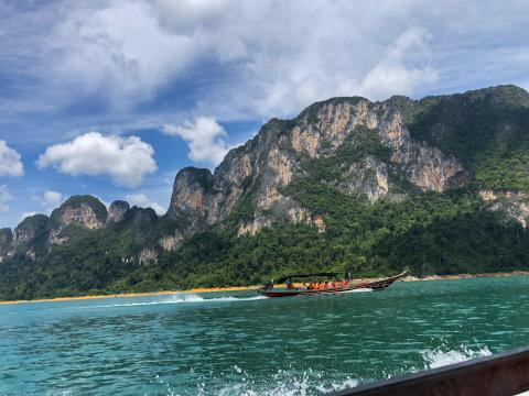 Image of small tour boats exploring Thailand's hidden wonders, surrounded by limestone cliffs and crystal blue water.